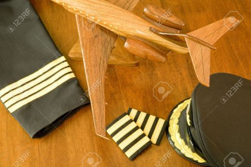 3387568-A-pilot-s-uniform-cap-and-a-wooden-aircraft-on-a-table-Stock-Photo.jpg